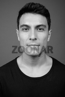 Young handsome Hispanic man against gray background