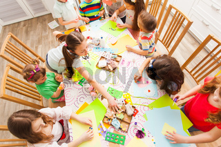 Group of children around the table making postcards together