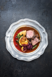 Traditional saddle of venison with fried mashed potatoes and red cabbage in game red wine sauce as top view on a pewter plate with copy space
