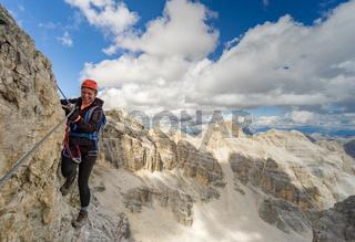 attractive blonde female mountain climber on a steep Via Ferrata in the Italian Dolomites