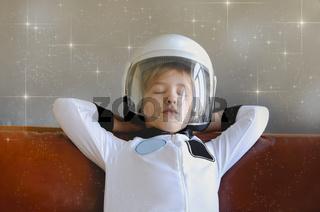 Astronaut futuristic kid girl with white full length uniform and helmet on the sofa
