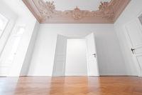 open  door in empty room of historic apartment after refurbishment