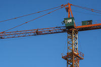 Tower crane against blue sky on a construction site for building of multi storage building or another type of structure.