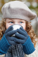 Girl in grey beret drinking from flask cup