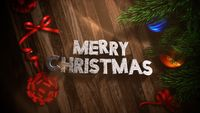Merry Christmas text, gift boxes and green tree branches with balls on wood background