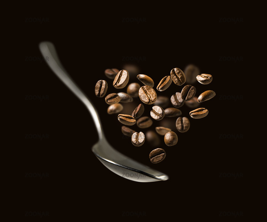Coffee beans in the shape of a heart and a spoon in flight