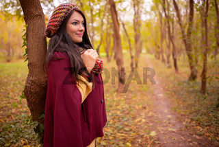 Beautiful girl in stylish autumn fashion clothes, in park scenery with trees and leaves. Gorgeous romantic young woman outdoors. American plan shot in warm natural light, retouched, vibrant colors