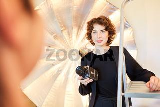 Junge Fotografin mit Mittelformatkamera im Fotostudio