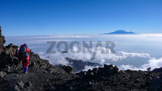 climbers hike down from the summit of Mount Meru in Arusha National Park in Tanzania