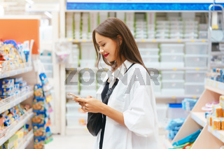 Smiling young woman with smartphone in supermarket