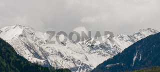 panorama mountain landscape with snowcapped peaks and expressive cloudscape
