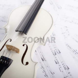 Close view of a violin and musical notes on white wooden table