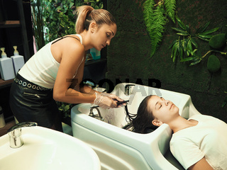 Cheerful young teen girl enjoying head massage while getting her hair washed by a professional hairdresser