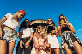 Five young women have fun at the car park.