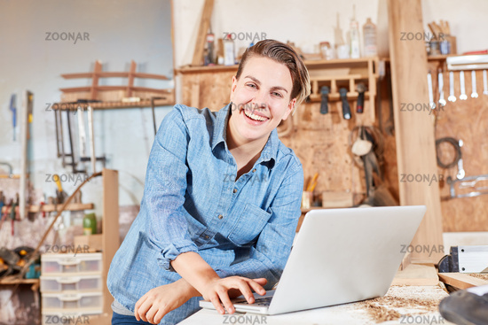 Frau als Tischler Azubi am Laptop Computer