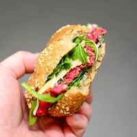 Hand Holding a Beetroot Burger with Arugula