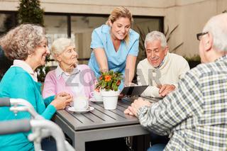Pflegekraft mit Tablet und eine Gruppe Senioren