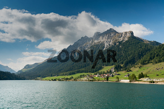 view of an idyllic and picturesque turquoise mountain lake surrounded by green forest and mountain peaks in the Swiss Alps