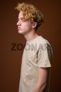 Skinny young man with curly hair against brown background