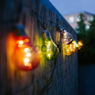 Colorful light bulbs on a urban terrace or a balcony at night. Eventing