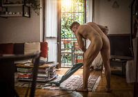 Nude muscular man cleaning floor in apartment