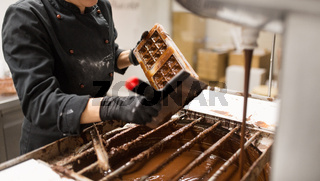 confectioner cleaning chocolate mold by spatula