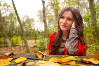 Beautiful romantic girl in park autumn scenery, sitting down at a wooden table covered with yellow leaves, looking away. Gorgeous young woman outdoors. Close-up shot in natural light, vibrant colors