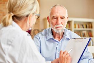 Ärztin befragt Senior als Patient in der Anamnese