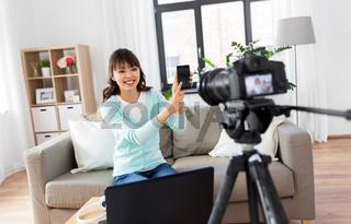 female blogger makes video blog of smartphone