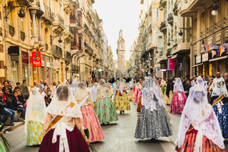 Valencia, Spain - March 17, 2019: Several of the thousands of women Falleras who parade down the street of La Paz with their typical Valencian Spanish dresses during the offering of Fallas to the Virgin, seen from behind.