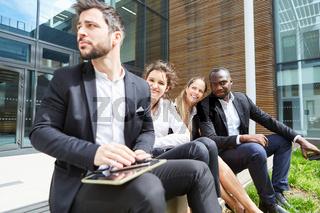Business Team macht Pause vor dem Büro