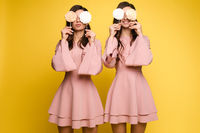 Charming twins closing eyes with lollipops and posing