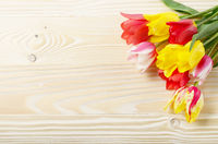 Bunch of Colorful tulip flowers on wooden table background with space for text
