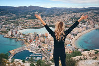 Climbed up on peak of Penon de Ifach woman raised her hands enjoy picturesque cityscape and beautiful nature view from above, rear view. Tourist and landmark, feeling of freedom concept. Calpe, Spain