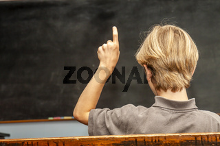 Concept of public primary school education with young boy raising his hand in the classroom