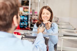 Kundin an Supermarkt Kasse zahlt mit Kreditkarte