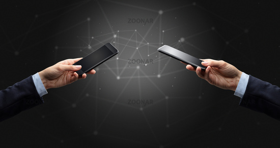 Close up of two hands holding smartphones