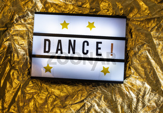 Text Dance on white illuminated board. Conceptual message for entertainment.