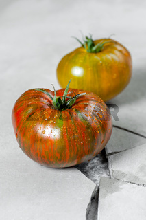 Hereditary tomatoes. Two tomatoes of different colors on a gray concrete table with a crack.