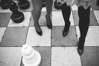 Women standing on bricks with chess board pattern.