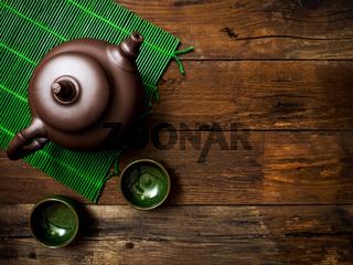 Teapot on green bamboo mat. Top view