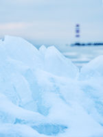 Lighthouse at jetty on the lake in winter