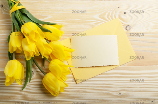 Yellow tulips near blank greeting card and envelope on natural wooden background with space for text