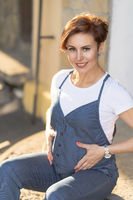 Pregnant Woman In Blue Denim Overalls Sits On The Parapet