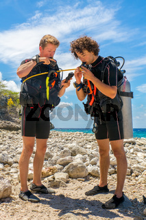 Two divers checking diving equipment at beach