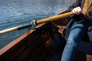 Young woman using paddle on a wooden boat - Lake Bled Slovenia rowing on wooden boats