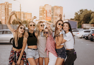 Six young women have fun at the car park.