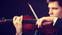 Man man dressed elegantly playing violin
