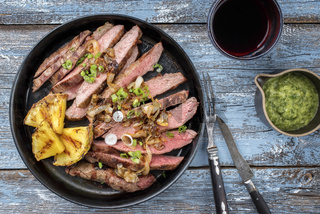 Barbecue dry aged wagyu flank steak with pineapples and chimichurri sauce as top view on a plate