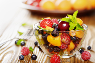 Assorted fruits in glass bowl on kitchen wooden table with fork aside